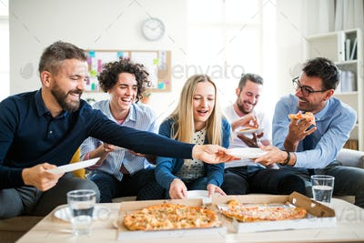 Group of young businesspeople with pizza having lunch in a modern office.