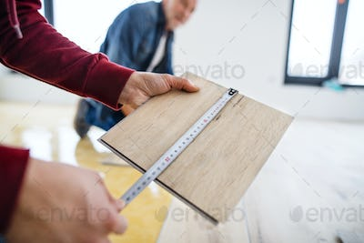 A midsection of mature man with his senior father laying vinyl flooring, a new home concept.
