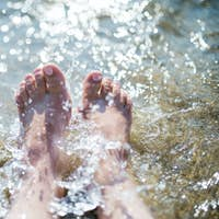 Close-up of female feet in water on beach, summer holiday concept.