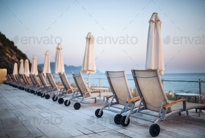 Beach chairs and umbrellas on tropical beach, summer holiday concept.