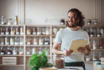 A young male shop assistant standing in zero waste shop, checking stock.