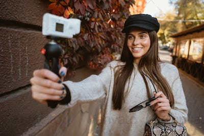 Cute, young female blogger posing on camera