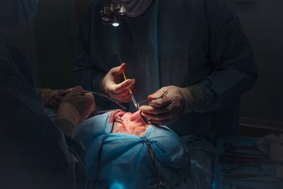 Surgeon and his assistant performing cosmetic surgery on nose