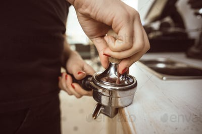 Barista presses ground coffee using tamper. Close-up view on hands