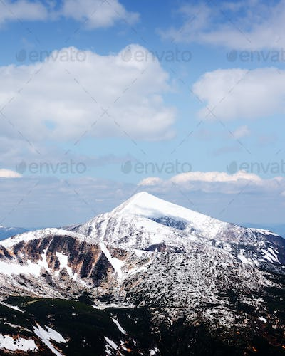View of the stony hills with snow and blue sky