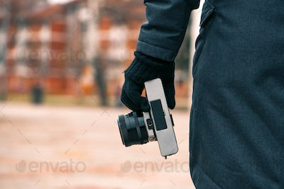 Hipster female photographer holding vintage SLR camera on street