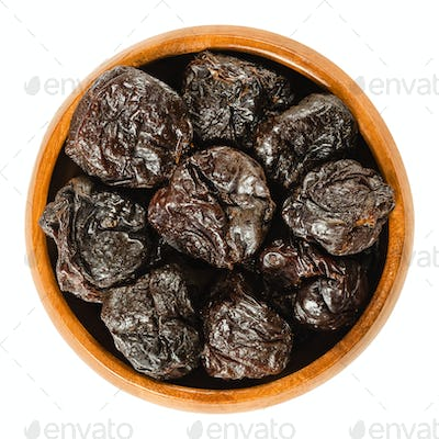 Prunes, dried plums in wooden bowl over white