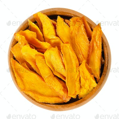 Dried mango strips in wooden bowl over white