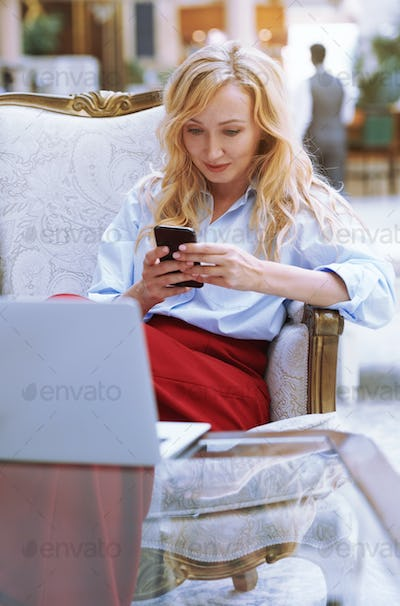 Businesswoman Using Smartphone in the Modern Bank Lobby