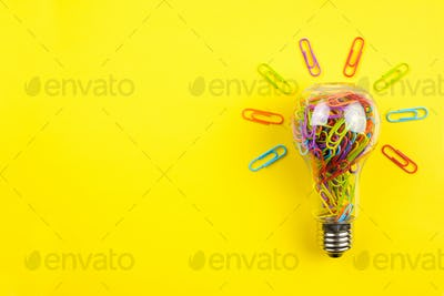 Light bulb filled with colorful paper clips