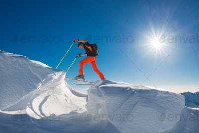 A man alpine skier climb on skis and sealskins  in so much snow
