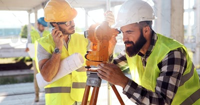 Team of construction engineers working on building site