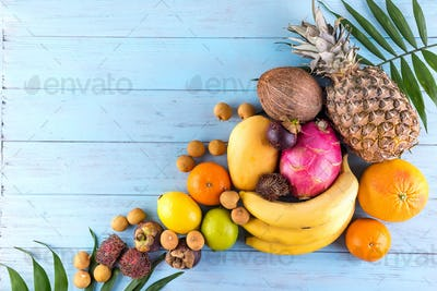 Ripe juicy tropical summer seasonal fruits on palm Leaf on blue wood background. Vacation healthy