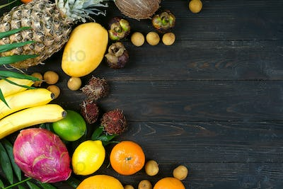 Summer colorfull concept border with tropical fruits and leaves, flat lay, space for a text