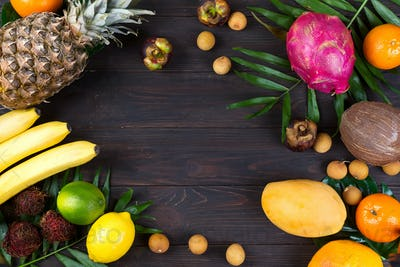 Tropical fruits frame with palm leaves on a dark wooden background, flat lay copy space