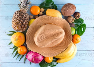 Summer composition. Tropical palm leaves, hat, many fruits on blue wooden background. Summer concept