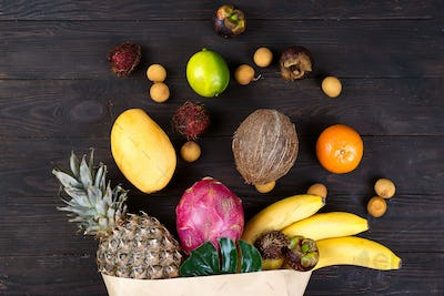 Paper bag of different healthy tropical fruits on dark wooden background. Top view