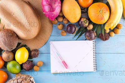 Summer composition. Tropical palm leaves, hat, many fruits on blue wooden background. Concept