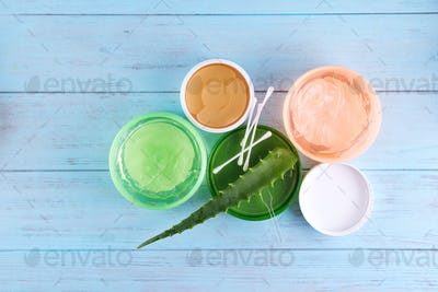 gel of snail, eye patch and Fresh Aloe Vera Gel in jar on blue wooden background. Snail gel is