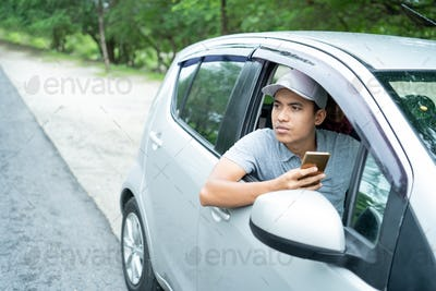 male driver searching location when looking for destination with smartphone