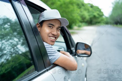 asian young man driver look back from the open windows look at the camera