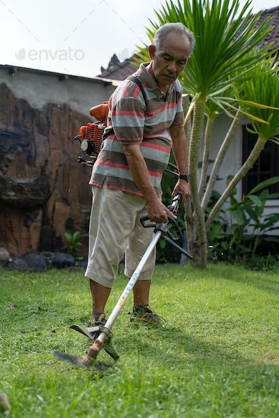 senior asian man mowing grass at his own home garden