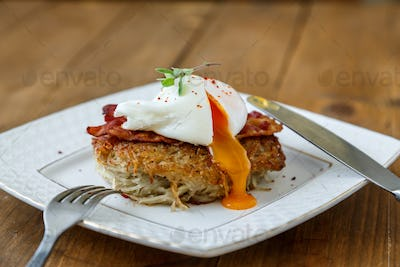 Potato rosti, poached egg with runy yolk and bacon on top
