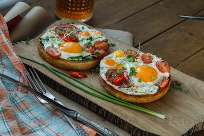 Two toasted bread with sunny side fried egg and tomato