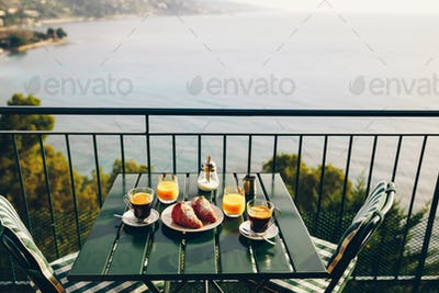 Delicious breakfast with coffee, pastry, and orange juice served on the balcony with sea view.