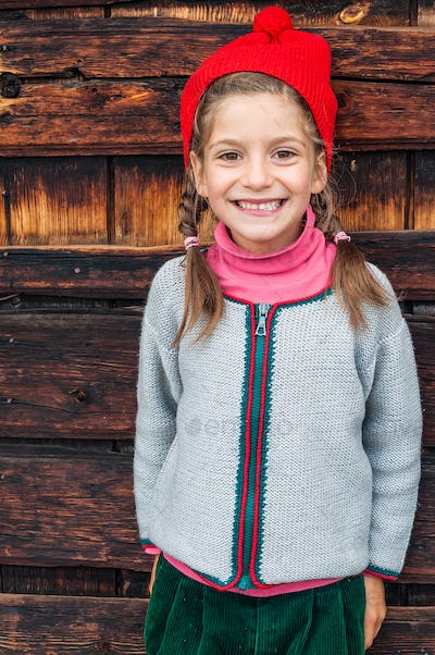 Summer holidays in the mountains a little girl in typical alpin