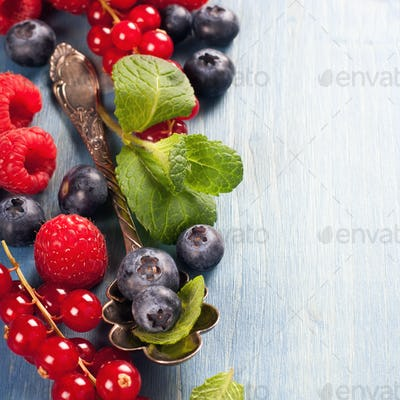 Berries and vintage spoon on a blue background