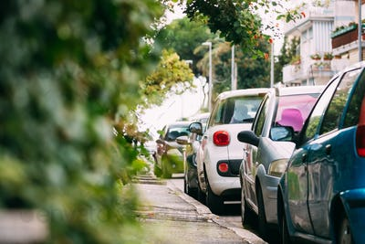 Cars Parked On Street In European City In Sunny Summer Day