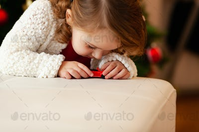 Little child plays with little toy car.