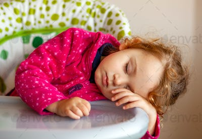 Exhausted little girl asleep in the high chair