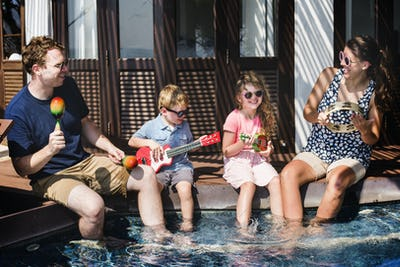 Family playing music by the pool