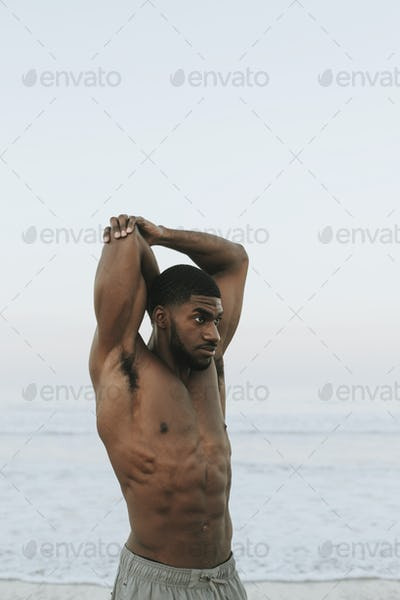 Fit man stretching at the beach