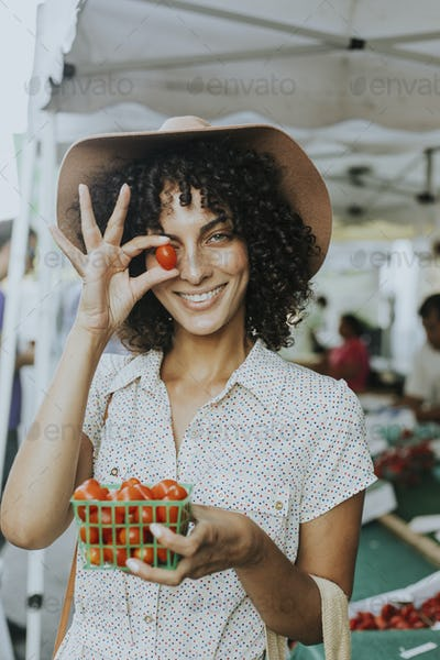 Beautiful woman buying tomatoes at a farmers market