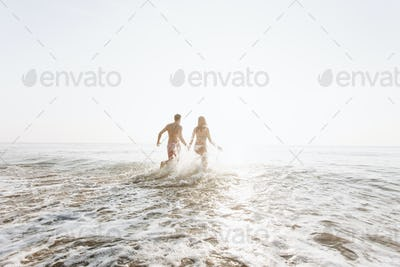Happy couple running into the water