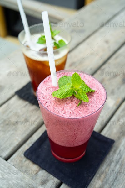 a pink strawberry smoothie with mint leaf on the wooden table