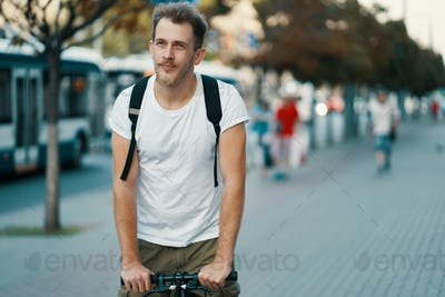 A man riding a bike in an old European city outdoors