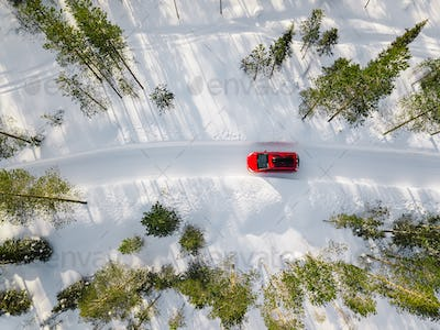 Aerial view of red car driving through the white snow winter forest on country road in Finland