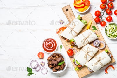 Burritos tortilla wraps with beef and vegetables on white background.