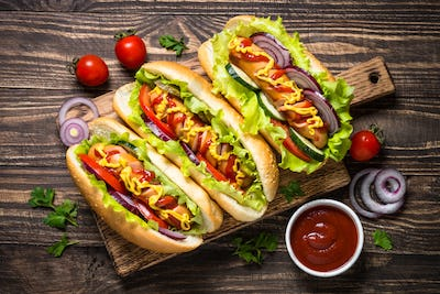 Hot dog with fresh vegetables on wooden table.