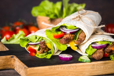 Burritos tortilla wraps with beef and vegetables.