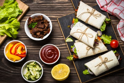 Burritos tortilla wraps with beef and vegetables top view.
