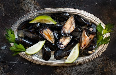 Fresh uncooked  italian mussels with lime and parsley top view