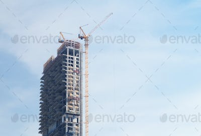 Skyscraper under construction with crane on blue sky background