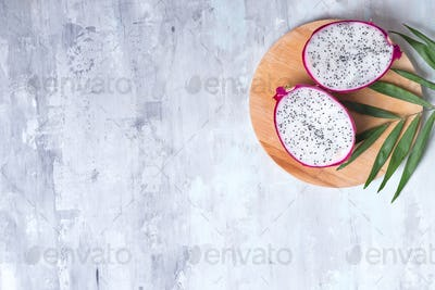 Pitaya or Dragon Fruit with palm leaf on wooden round plate on gray stone background with copy space