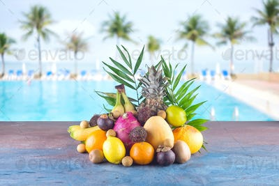 Assorted tropical fruits on the beach orange , pineapple, lime, mango, dragon fruit, orange, banan