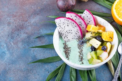 breakfast kiwi smoothie bowl topped with pitaya, pineapple, chia seeds and berries with palm leaf on